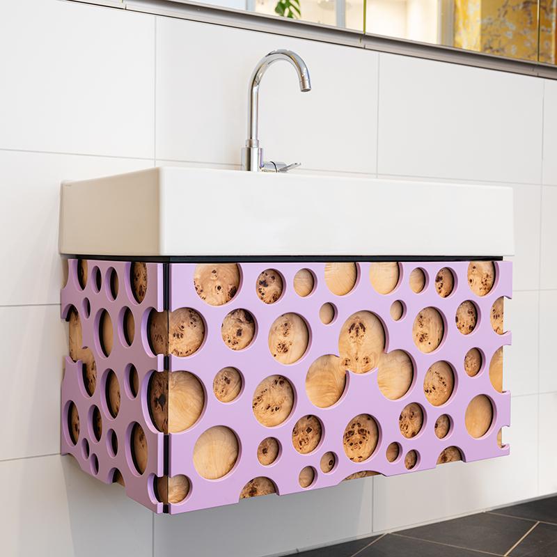 Der außergewöhnliche und verspielte Waschtischunterschrank ist ein echter Badezimmer-Hingucker. Das ausgefallene Design erinnert mit seinen kreisrunden lavendelfarbigen Formen an ein heißes Schaumbad.