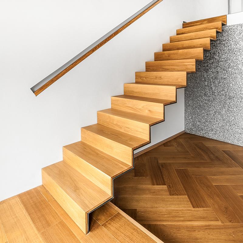 Die schlichte Treppe ohne Stütze mit eingelassenem Handlauf fügt sich mit klarem Design ideal in die moderne und stilechte Dachgeschosswohnung ein.