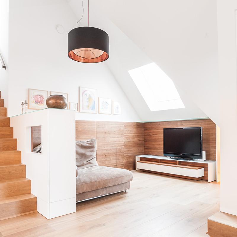 Die gemütliche Loungeecke aus vertäfeltem Nussbaum und integriertem TV Schrank bringt Wärme und Gemütlichkeit in das helle und geräumige Loft. Es entsteht ein schöner Rückzugsort.