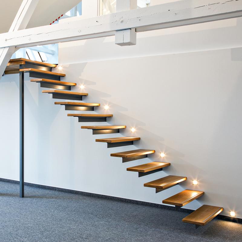 Die freitragenden Treppenstufen aus Eiche massiv und dem dazugehörigen Treppenpodest fügen sich mit ihrem minimalistischen Design sehr harmonisch und zurückhaltend in den großen Büroraum ein.