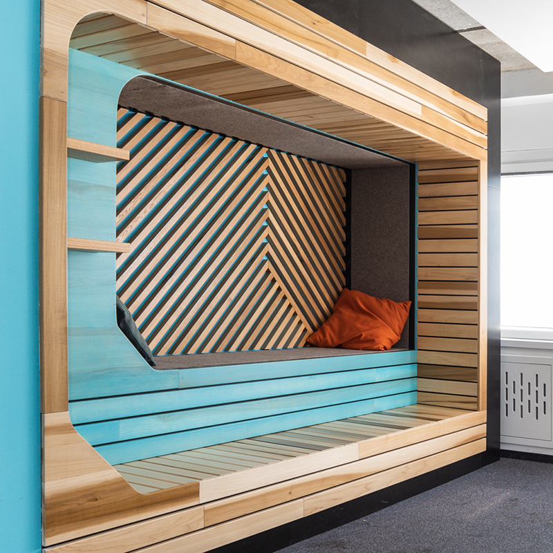 Dieser gemütliche Loungebereich aus Eiche, Filz und Espe ist dem Look einer Sauna nachempfunden. Außerdem erinnert die Architektur der Saunabereiche an das kleinteilige Innenleben eines Kreditkartenchips – wie passend für eine Bank. Espe ist im Übrigen ein sehr beliebtes Holz, das für den Innenausbau von Saunen Verwendung findet. Filz ist für seine Leitfähigkeit von Wärme und Schallisolierung bekannt ist. Diese kleine Rückzugsinsel bietet Zeit für Ruhe und Erholung zwischen der Arbeitszeit und sorgt für ein behagliches Wohlgefühl.
