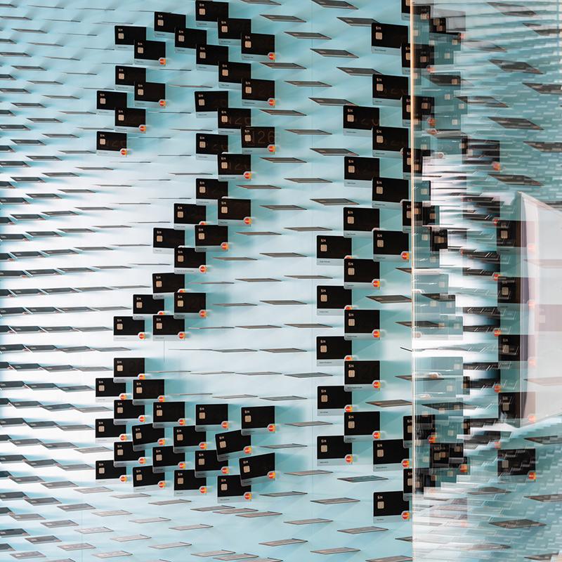 Diese Wandvertäfelung, die aus einer Vielzahl an Kreditkarten besteht, ziert die Wand einer Berliner Bank. Die Karten sind in unterschiedlichen Winkel angeordnet, wodurch eine fließende, sehr organische Bewegung entsteht. Sie ergeben zum einen den Namen des Unternehmens und stehen zum anderen für die Gesamtanzahl aller Mitarbeiter.
