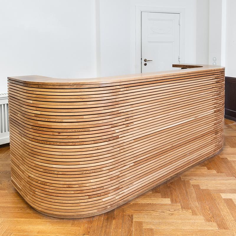Dieser schöne Empfangstresen aus Eiche Massiv schmückt den Eingangsbereich eines Softwareunternehmens und sorgt mit seiner Materialität und Farbigkeit für eine gemütliche Atmosphäre. Dieses Möbelstück sieht nach wirklich präziser Handarbeit aus.