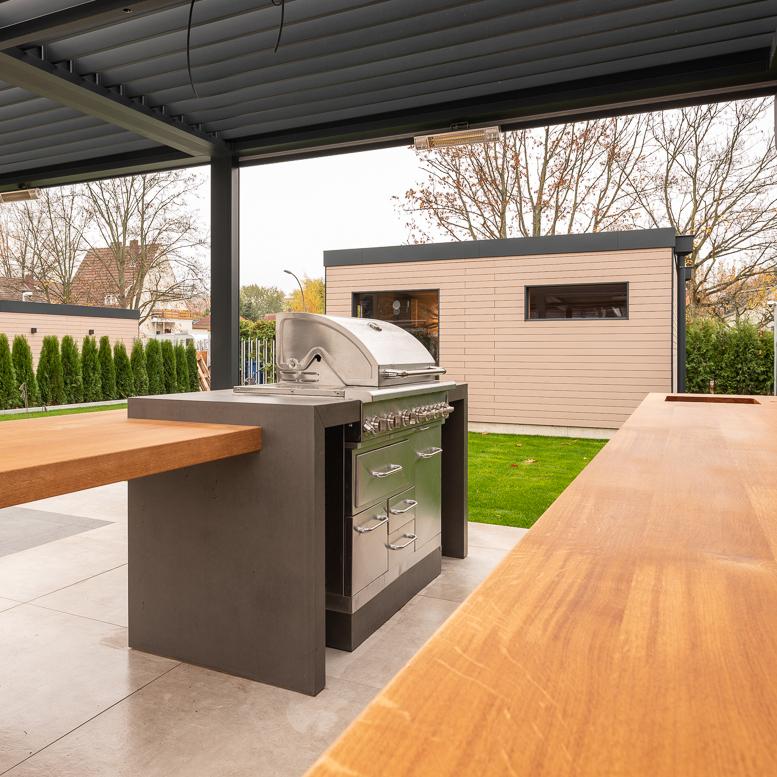 Diese sehr moderne und individuelle Gartenküche in minimalistischem Design sorgt für viel Stauraum und bietet mit einer ausladenden Arbeitsplatte unglaublich viel Platz zum Zubereiten von leckeren Speisen. Die maßgeschneiderte Außenküche ist gerade an warmen Sommertagen eine willkommene Abwechslung zur Küche im Haus oder in der Wohnung, denn besonders im Sommer isst man doch sowieso viel lieber draußen im Garten. Die top ausgestattete Küche mit Gasgrill, Küchenkorpussen aus Edelstahl und imi-Beton sorgen für das notwendige BBQ-Flair auf der Terrasse. Die hochwertige aber leichte Beton Imitation verleiht der Outdoor Küche einen echt coolen Look im Industrial Design. Selbst einen Hängeschrank für den Flachbildschirm hat dieser schönen Außenküche zu bieten. So steht einem gemütlichen Grillabend mit Public Viewing unter freiem Himmel nichts mehr im Wege. Und seien wir mal ehrlich: Wer würde bei so einem Anblick nicht auch viel lieber im Garten kochen? Diese Küche ist ein Traum für alle BBQ Liebhaber.
