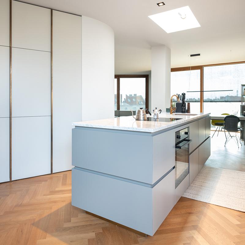 Diese tolle Küche in minimalistischem Design sorgt neben unglaublich viel Stauraum für einen gemütlichen Ort zum Wohlfühlen. Hinter dem edlen Wandschrank mit Griffen aus Messingwinkeln verbirgt sich ein Kühlschrank, eine Garderobe und natürlich viel Platz für andere Haushaltsutensilien.