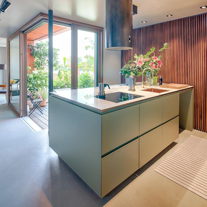 Diese luxuriöse Raumausstattung wird durch die Lamellenwand aus edlem Nussbaum und dem Raumtrenner, hinter dem sich nicht nur eine wunderschöne Treppe aus Eiche verbirgt, zu einem gemütlichen Raumwunder. Nebst Backofen und Kühlschrank findet man hier vor allem viel Stauraum für Töpfe und Co. Dank der klugen Raumaufteilung, dem Mix unterschiedlicher Materialien und Farben wird die Küche zu einem echten Wohlfühlort. Sogar die Terrakotta- und Grüntöne von draußen, finden sich hier wieder.