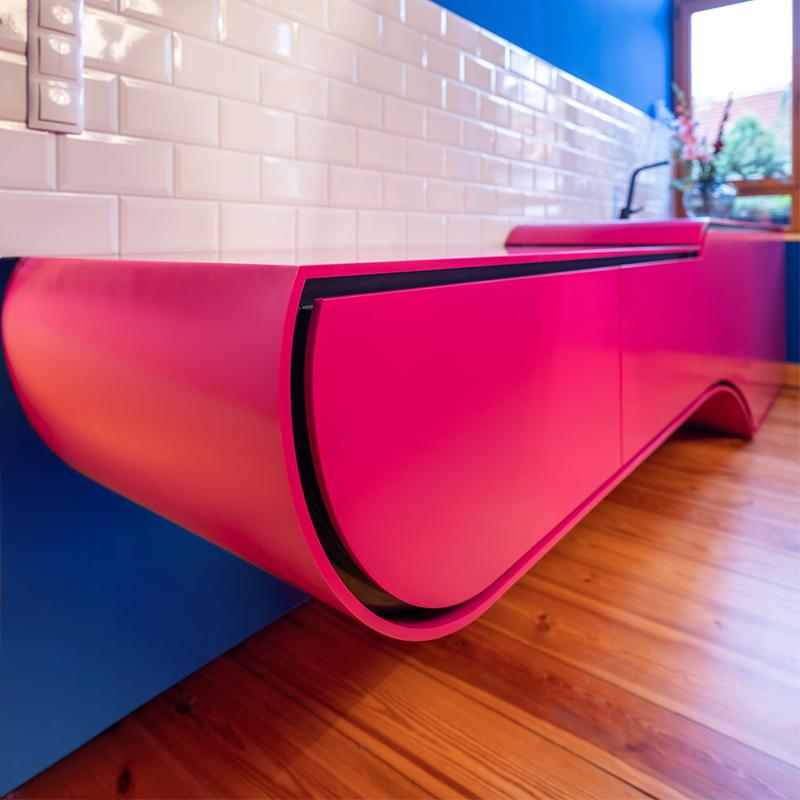 Die elegant geformte Küche aus pinkem Corian verkleidet Kühlschrank, Geschirrspüler und Induktionskochfeld im einmaligen Case Design. Die Fläche neben dem Spülbecken lässt sich auf einer Führung verschieben und gibt so das Kochfeld frei. Die L-Profil-Griffleiste hinter Schubfächern und Türen sorgen für ein minimalistisches Frontdesign. Das schwarze MDF des Korpus schafft durch den hohen Kontrast zum Pink eine dynamische Formsprache – wie ein schnittiges Spaceship.