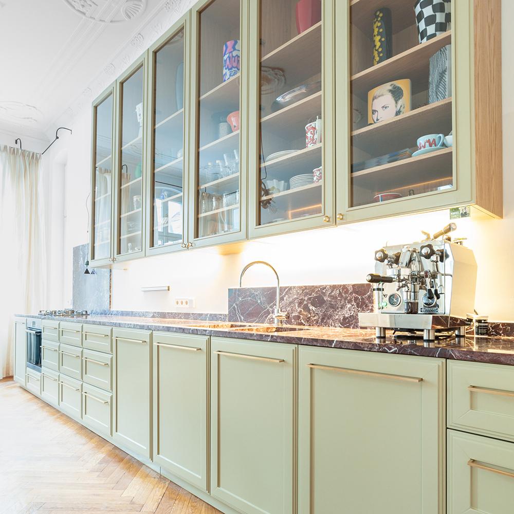 Diese edle Küche sorgt nicht nur mit ihrem Materialmix aus Holz, Stein, Messing und Glas für ein gemütliches Wohngefühl. Auch die Farbwelt aus Bronze, Braun und einem leichten Grün verbreitet eine wohlige Atmosphäre.