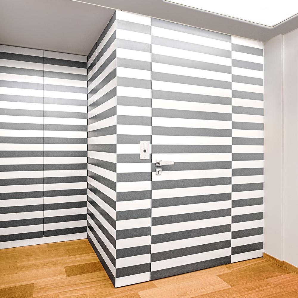 Die auffällige Wandvertäfelung in Schwarz-Weiß lässt erst auf den zweiten Blick erahnen, dass sich dahinter eine Tür zum Fahrstuhl verbirgt. Ein wahres Raumwunder, das sich wie ein Gemälde einfügt.