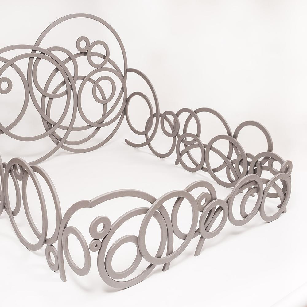 Das außergewöhnliche Farben- und Formenspiel dieser Bettverkleidung erinnert an eine metallene Skulptur. Die Ringe wirken aufgrund ihrer individuellen Anordnung schwebend und leicht wie auf Wolken.