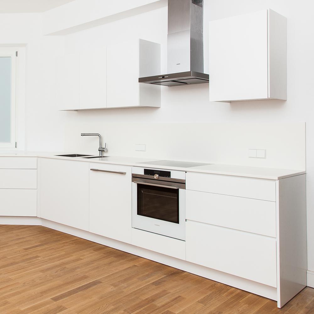 Diese Einbauküche in zurückhaltendem, modernem Design zaubert eine gemütliche Atmosphäre in die dunkle Küche zum Hinterhof.