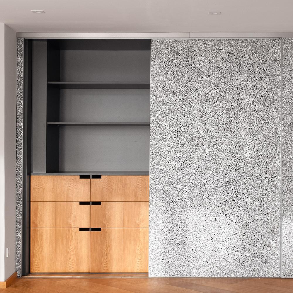 Der außergewöhnliche Wohnzimmerschrank, der geschlossen wie eine extravagante Wandverkleidung daherkommt, hält unheimlich viel Stauraum bereit. Er ist nicht nur außen, sondern auch innen – mit Schubkästenfronten aus Eiche – ganz schön hui.