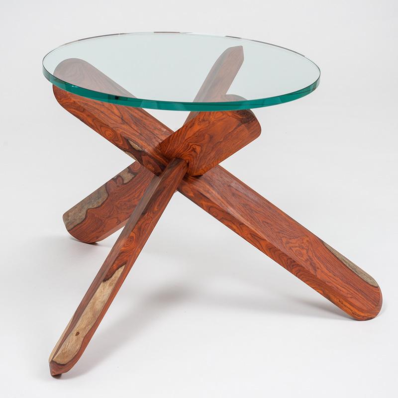 Der Beistelltisch aus dunklem Cocobolo Holz und einer Tischplatte aus Floatglas sorgt für ein warmes und gemütliches Wohnambiente. Er erinnert mit seinen drei ineinandergesteckten Beinen an ein 3-D-artiges Holzspielzeug für Kinder und wirkt dadurch sehr lebendig.