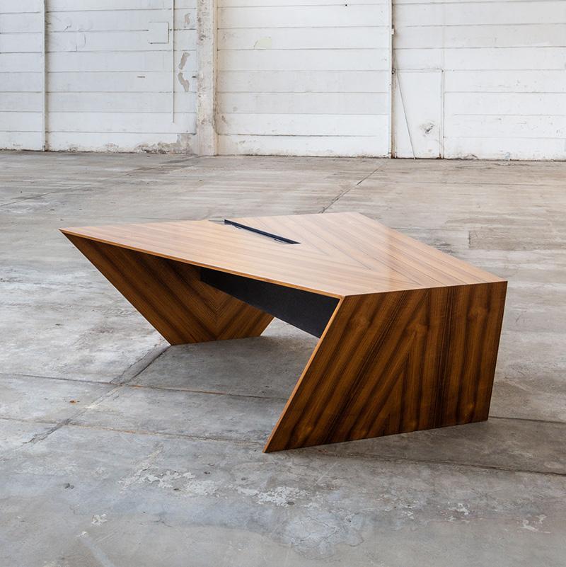 Der edle und hochwertige Schreibtisch aus Teak Furnier ist ein sehr individuelles Büromöbel. Das Design ist einem typischen Yachtdeck aus Teakholz nachempfunden. Der schöne Tisch bietet je nach Bedarf Platz für zwei bis vier Personen und ist ein echtes Highlight für jedes Büro. Der teilbare Bürotisch im Stil eines Yachtdecks wurde aus Teak Furnier gefertigt und setzt sich aus zwei Modulen zusammen. Durch die spitz zulaufenden Arbeitsflächen ist eine angemessene Privatsphäre für die Beschäftigten gegeben. An der äußeren breiteren Kante des Tisches befindet sich ein aus CDF (Compact Density Fibreboard) gefertigter Kabelkanal mit Deckel, der störende Kabel elegant verschwinden lässt. Die schwarze CDF-Trägerplatte ist mit lackiertem Teak Furnier beschichtet und mit CNC-gefrästen Kannelluren (Rillen) versehen, die mit Epoxhidharz ausgegossen und anschließend lackiert sind. Mithilfe dieses Fertigungsverfahrens mutet die Platte der typischen Optik eines marinetauglichen Bodens an. Stellt man zwei Module aneinander, so ergibt sich aus Kabelkanal und Verbindungskorpus ein Kreuz, das sehr stark an die vier Himmelsrichtungen eines Kompasses erinnert. Teakholz ist übrigens ein sehr dichtes, festes und robustes Holz, das vor allem bei Schiffsbauern nicht nur aufgrund seines exklusiven Charakters ein äußerst beliebtes Material ist. Es ist widerstandsfähig gegen Sonneneinstrahlung und verhindert somit Verfärbungen durch Lichteinfall. Außerdem ist Teak ganz besonders resistent gegen Wasser.