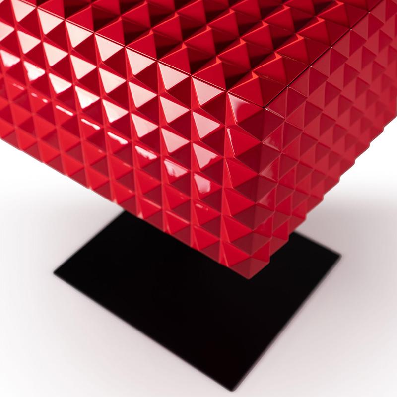Dieses individuelle High-End Hi-Fi Möbel in einem intensiven Kirschrot ist Kunstobjekt und Möbel zugleich. Mithilfe eines Servomotors lässt sich das Hubdeck aus dem mit kleinen Pyramiden versehenen Hochglanz Korpus herausfahren und bietet somit Platz für den Audioverstärker. Der Hi-Fi Cube– ein wahrer Hingucker fürs Wohnzimmer.