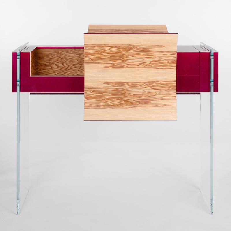 Dieses Designmöbel aus lackierter Olivesche ist wirklich bezaubernd. Die ausgefallene Farben- und Formensprache und die Auswahl hochwertiger Materialien setzen dieses besondere Möbelstück so richtig in Szene. Die zahlreichen kleinen Details wie die Massivholzadern aus Esche, die in umgekehrter Optik in Rot auch auf dem Holz wiederzufinden sind, beweisen, mit wie viel Know-how, Geduld und vor allem Liebe zum Detail das Möbel gefertigt wurde. Neben all der funkelnden Schönheit birgt dieses tolle Objekt aber auch die ein- oder andere Funktionalität. So gibt es eine Klappe, hinter der sich ein kleines Fach versteckt und einen Schubkasten, der sich gut als Geheimversteck eignet. Die Füße aus Glas verwandeln dieses Kunstwerk in ein schwebendes Objekt, das dadurch an Leichtigkeit gewinnt und jeden Raum zum Funkeln bringt. Wir sind ganz schön schockverliebt in dieses Teil: Nicht umsonst steht der Namenscode des Lackes für einen zuckersüß kandierten Liebesapfel.