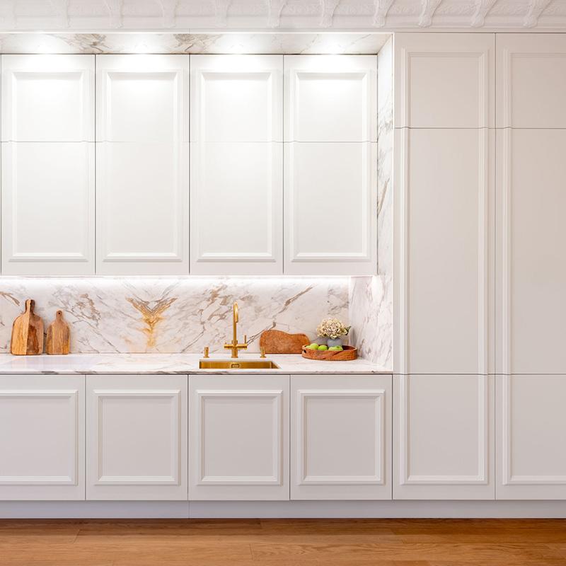 Diese extravagante und edle Küche mit einer Arbeitsplatte aus Marmor fügt sich sehr harmonisch in das Gesamtbild des Raumes ein. Durch den vorgezogenen Stuck wirkt die Küche wie in die Wand eingelassen. Die Küchenfronten mit aufgesetzten Profilleisten sind an den Wandstuck in luxuriöser Rahmenoptik angepasst und lassen den Raum dadurch größer wirken. Diese Küche besticht nicht nur durch Schönheit sondern ebenso durch Funktionalität und Alltagstauglichkeit. Sie bietet viel Stauraum – vor allem für sperrige Küchengeräte. Häufig wirken nämlich selbst aufgeräumte Küchen unaufgeräumt. Das liegt meist daran, dass Küchenhelfer und geliebte Küchengeräte, die für den täglichen Bedarf genutzt werden, griffbereit auf der Arbeitsplatte stehen und somit einfach stören. Bei dieser Küche haben wir genau das nicht. So verbirgt sich beispielsweise hinter der großen Klapptür eine beleuchtete Kaffeebar, die clever verstaut ist, aber dennoch griffbereit für den täglichen Bedarf bereitsteht. Und das Beste daran ist, dass die Arbeitsfläche auch wirklich als solche genutzt werden kann. Kühlschrank, Backofen, Wasch- und Spülmaschine sind voll integriert und verschwinden somit ganz elegant hinter den Küchenfronten. Unglaublich, wie ausgefallen und individuell eine Küchenzeile sein kann und gleichzeitig so zeitlos ist.