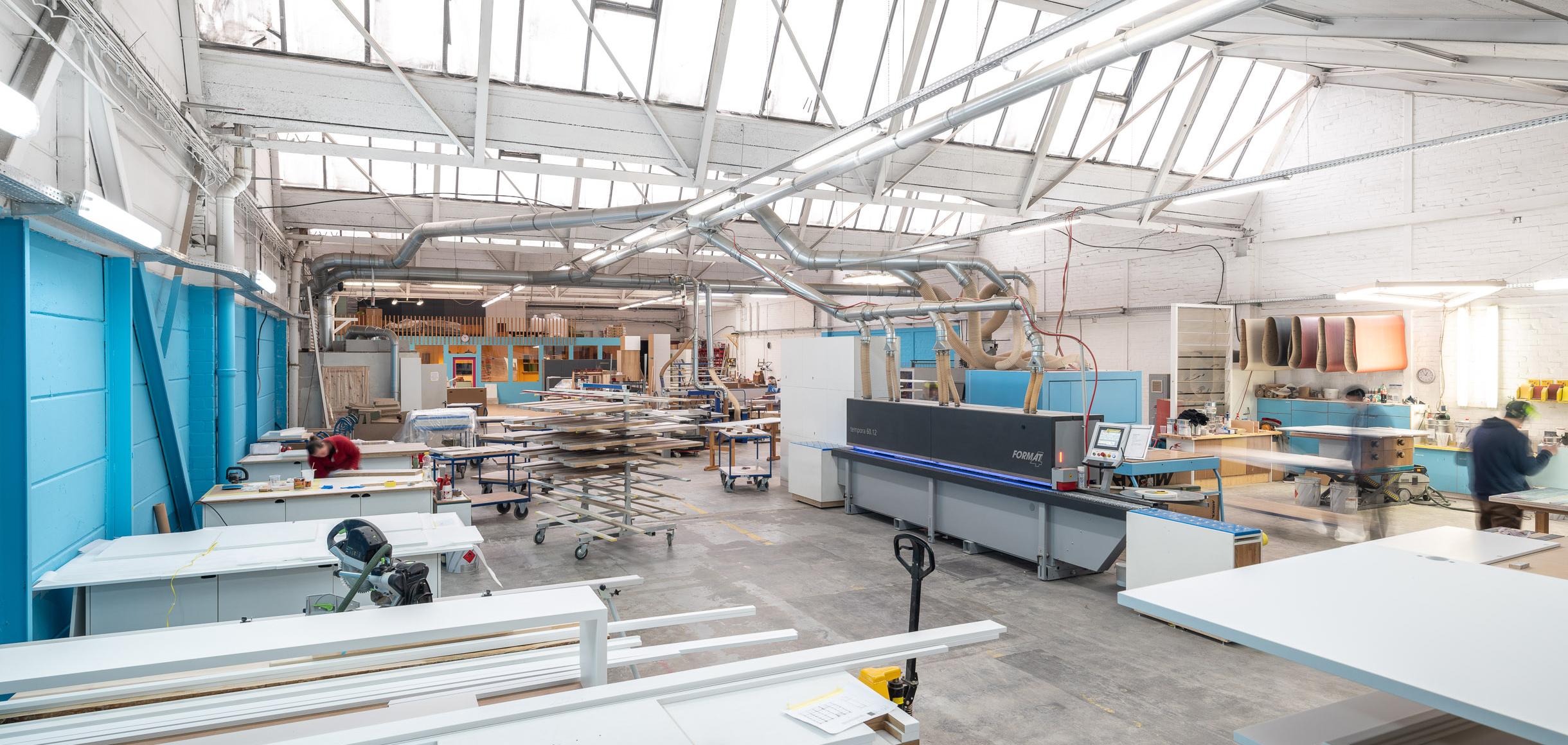 Ein Blick in unsere Werkstatt mit dem Meisterbüro, der Kantenanleimmaschine und den Plattenregal