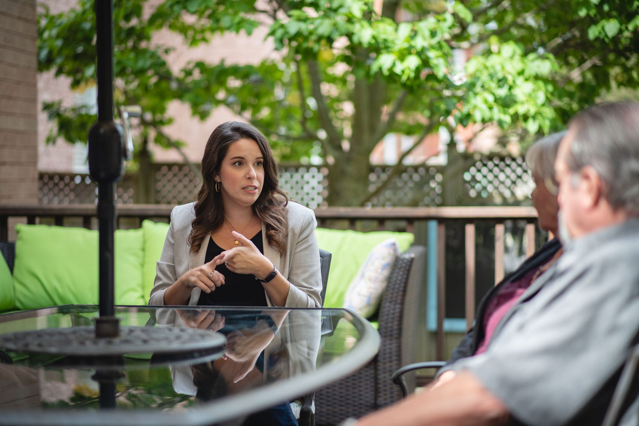 Mallory McGrath talking to a family at a patio table