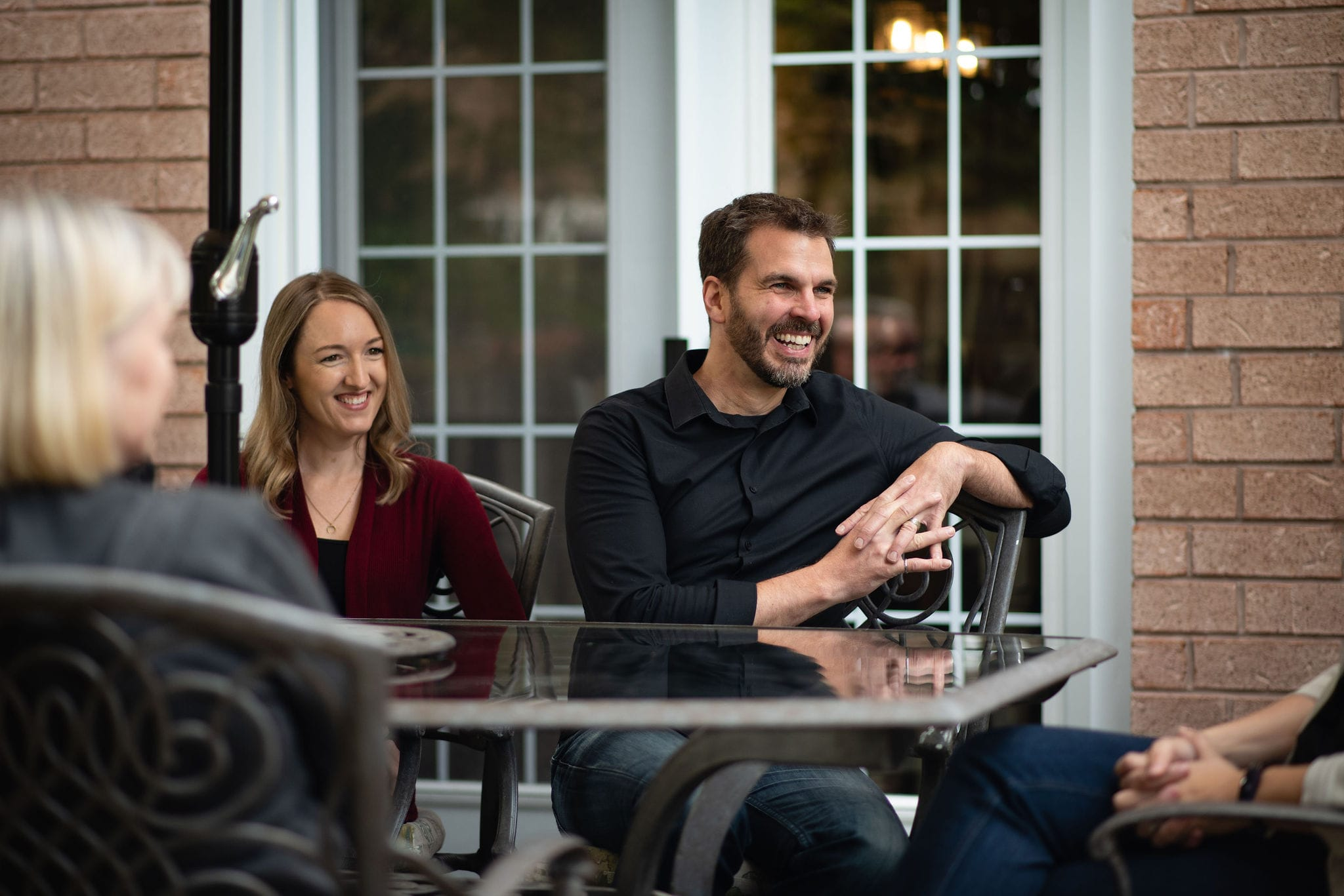 A smiling family at a patio table