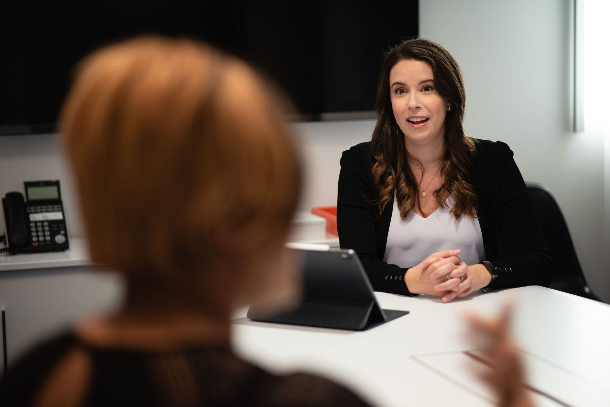 Mallory McGrath talking with a client in an office boardroom