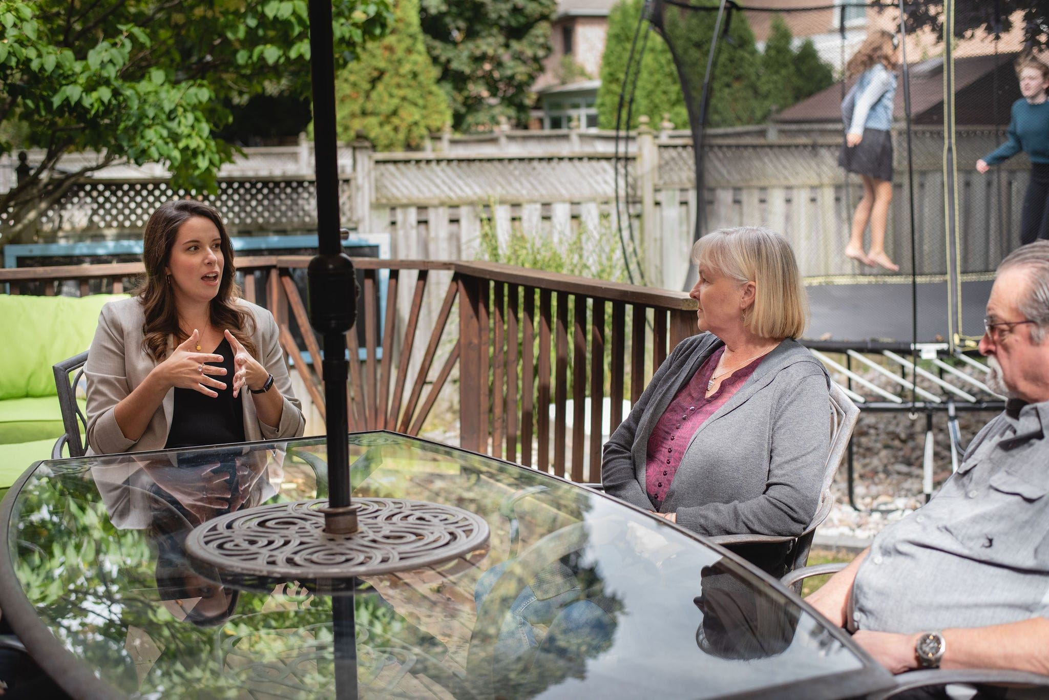 Mallory McGrath talking with a family at a patio table