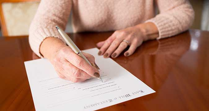 woman signing a Last Will & Testament