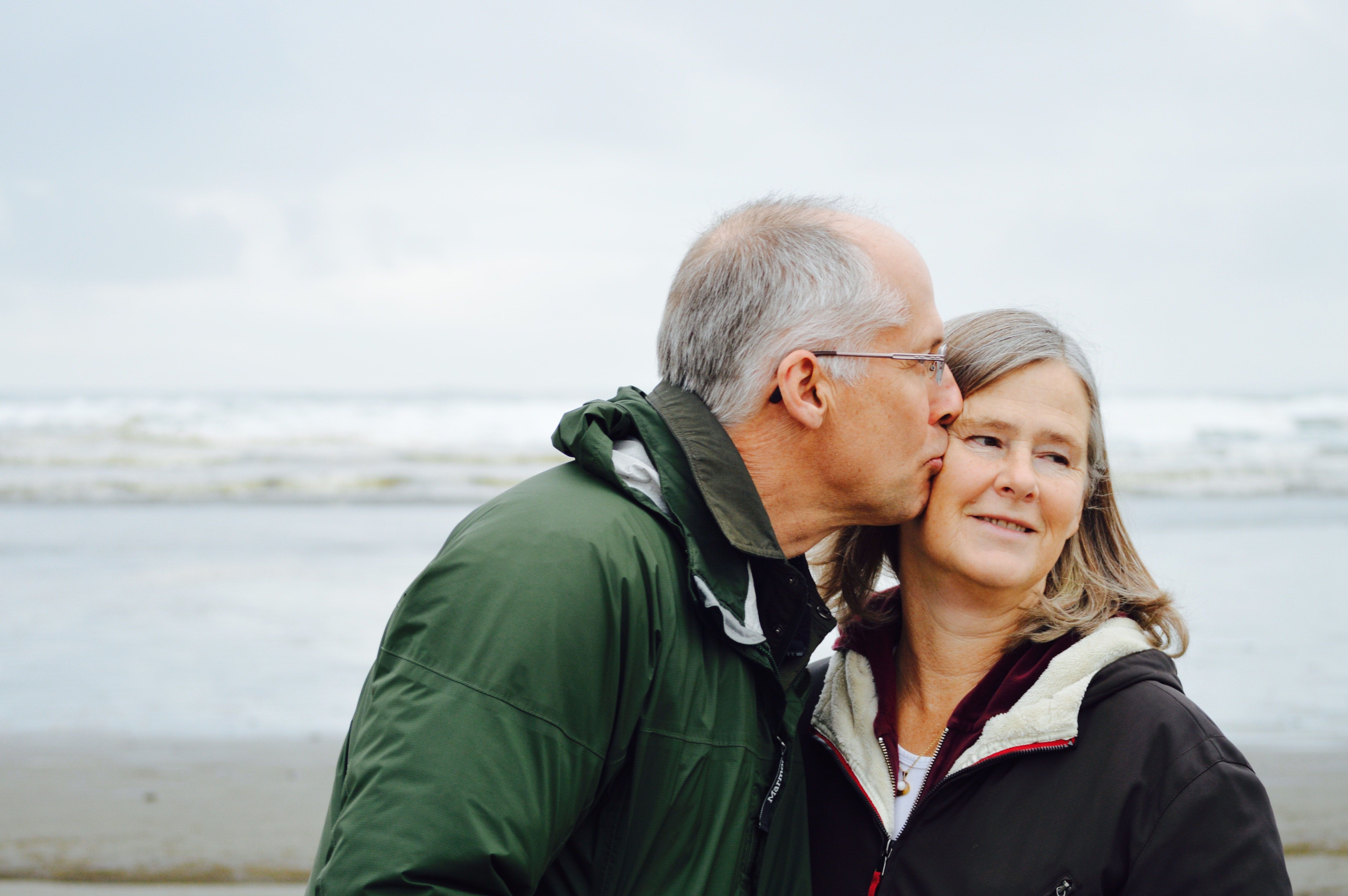 Middle-aged husband kissing wife's cheek