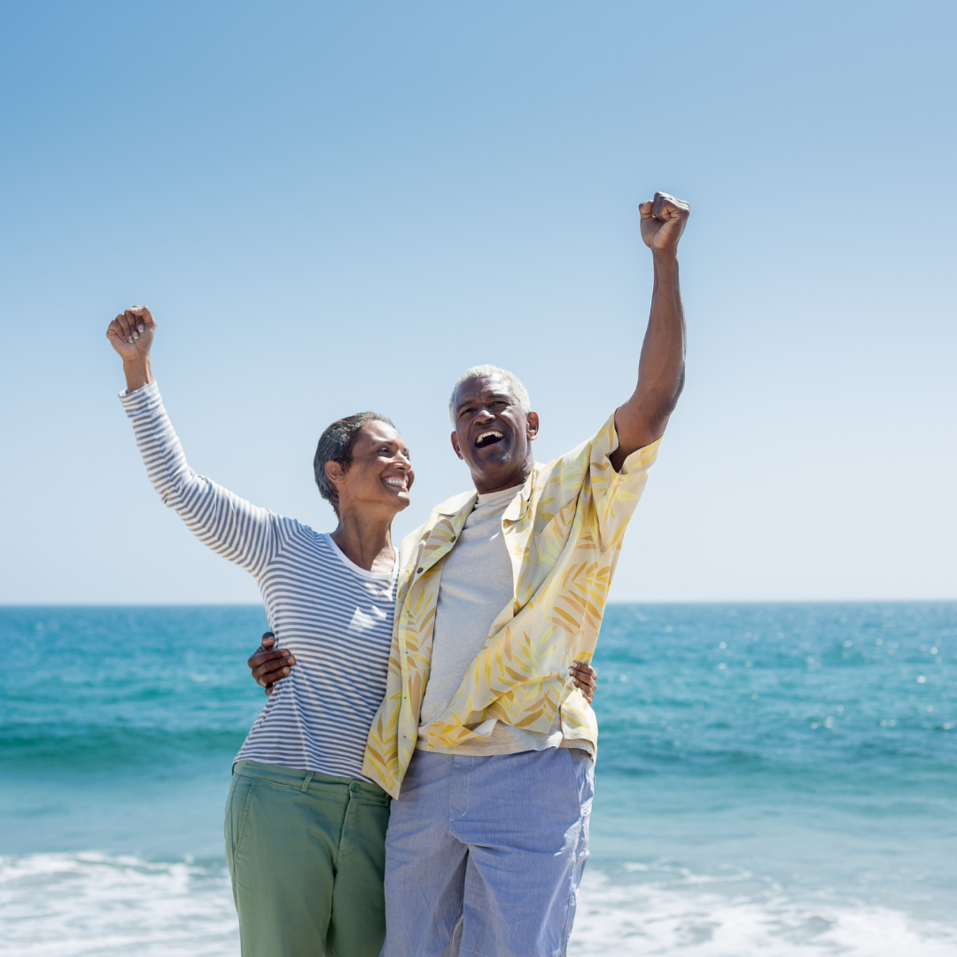 Adult heterosexual couple raising their arms in excitement while on a beach