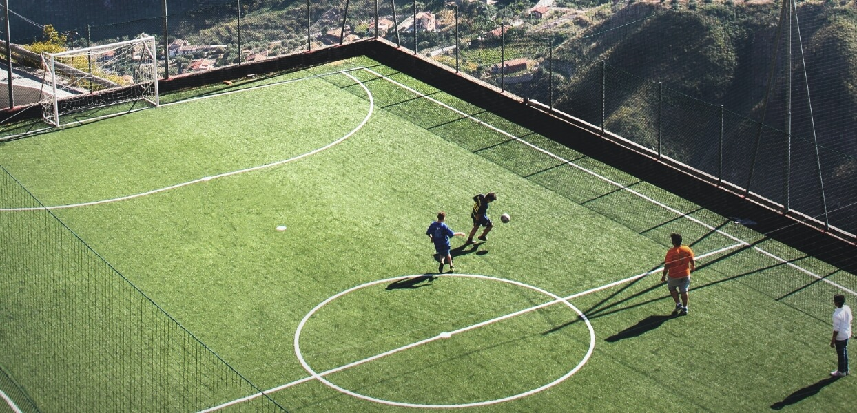 Four people playing football on a green football pitch.