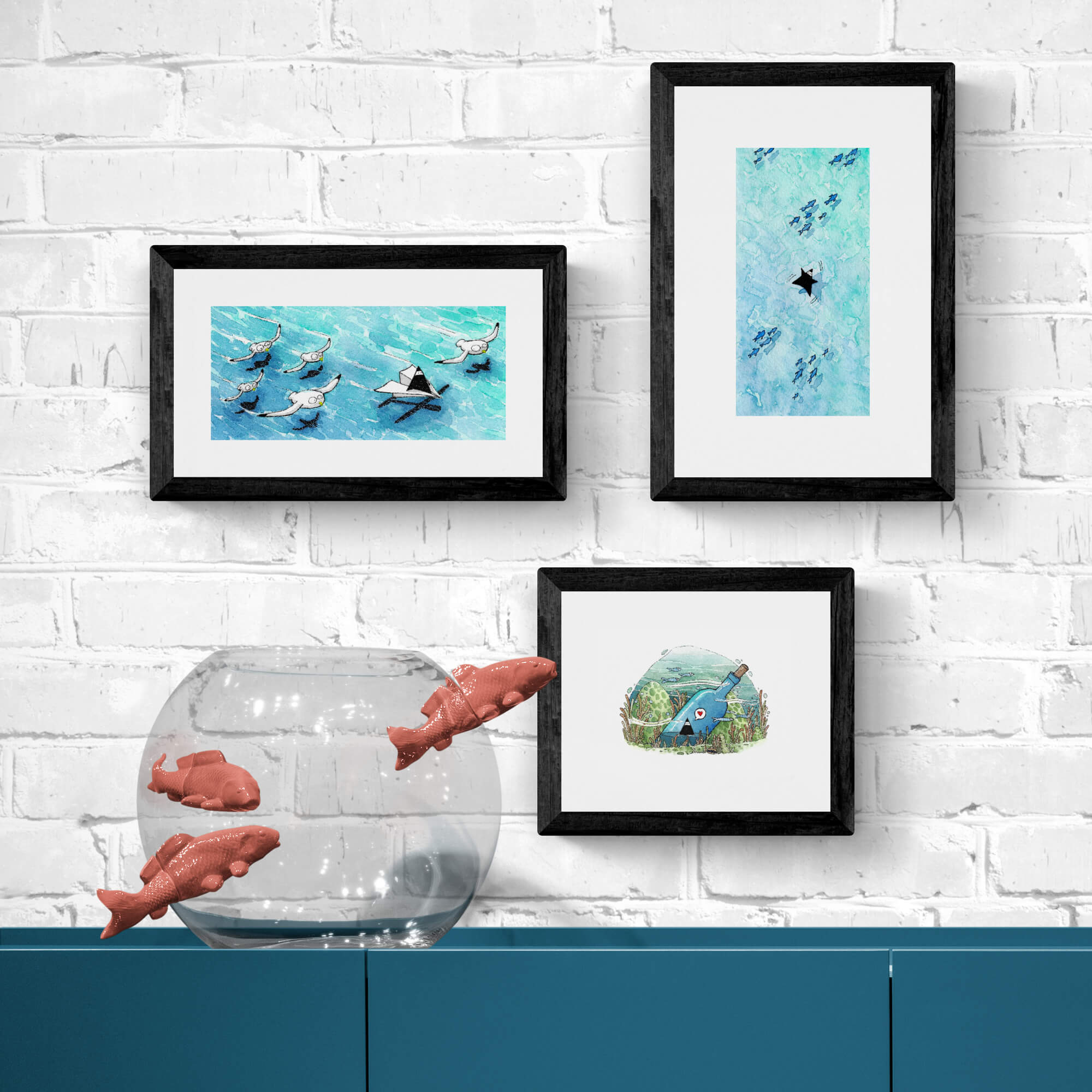 Three paintings above a piece of furniture with a fish bowl. The pictures are relaxing and reminiscent of summer holidays.