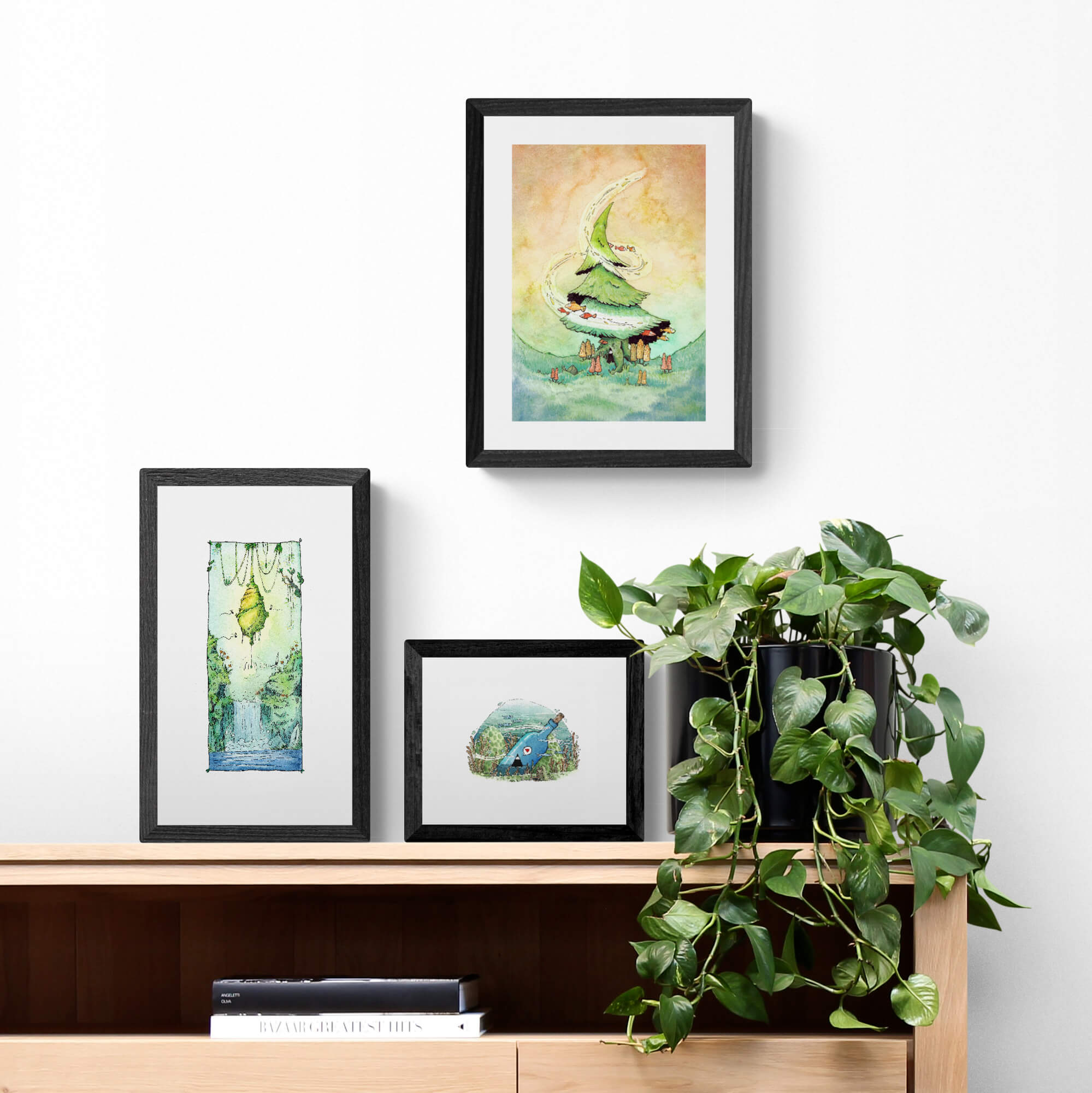 Three paintings on a sideboard with a plant. The pictures represent pleasant scenes.