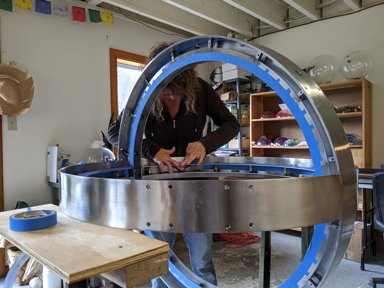 Artist taping blue tape to inside of metal sphere.