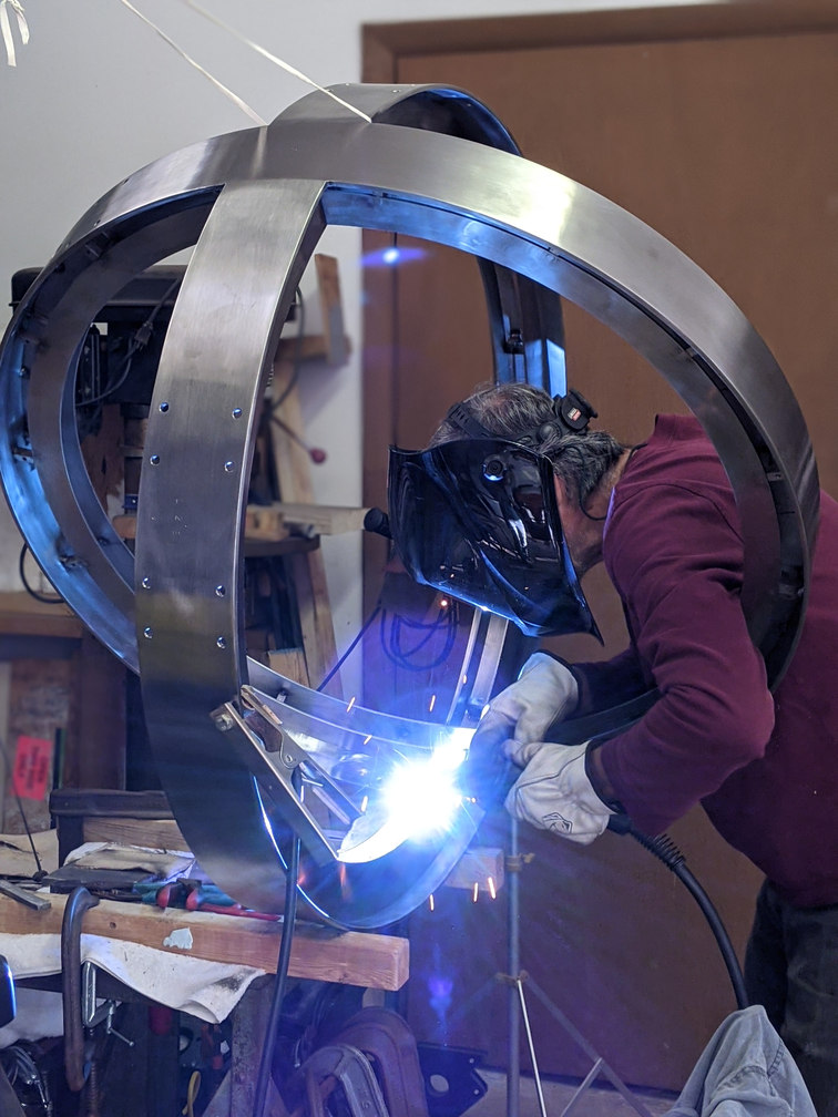 Artist with face shield welding metal sphere.
