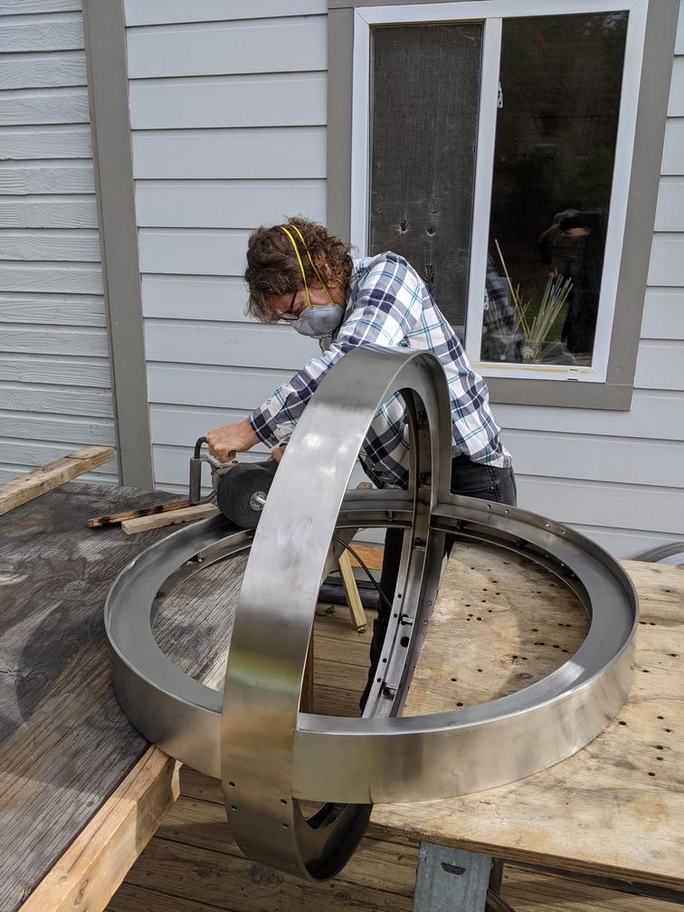 Artist buffing metal sphere with hand-held power tool.