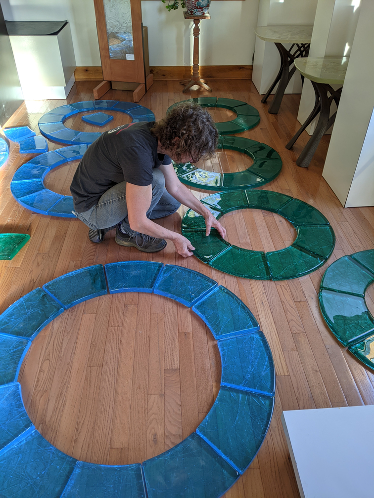 Artist placing blue and green cast glass into circles on floor.