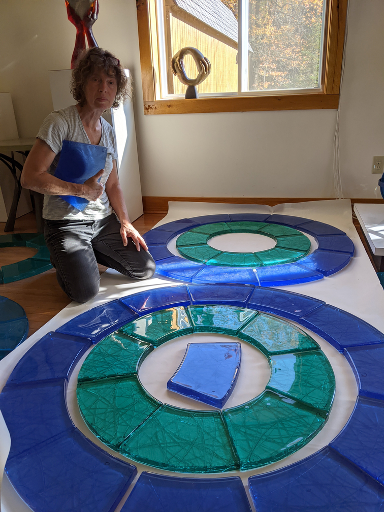 Artist with cast glass pieces of blue and green laid out in circles.