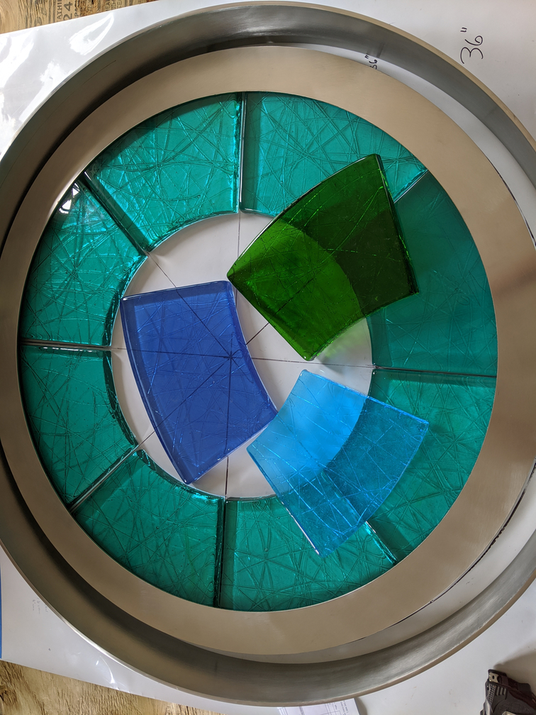 Glass samples in blues and greens arranged in a circle.