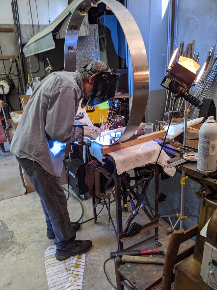 Artist wearing face shield welding metal hoop.