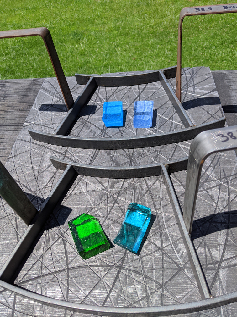 Thick green and blue cast glass samples in metal frames.