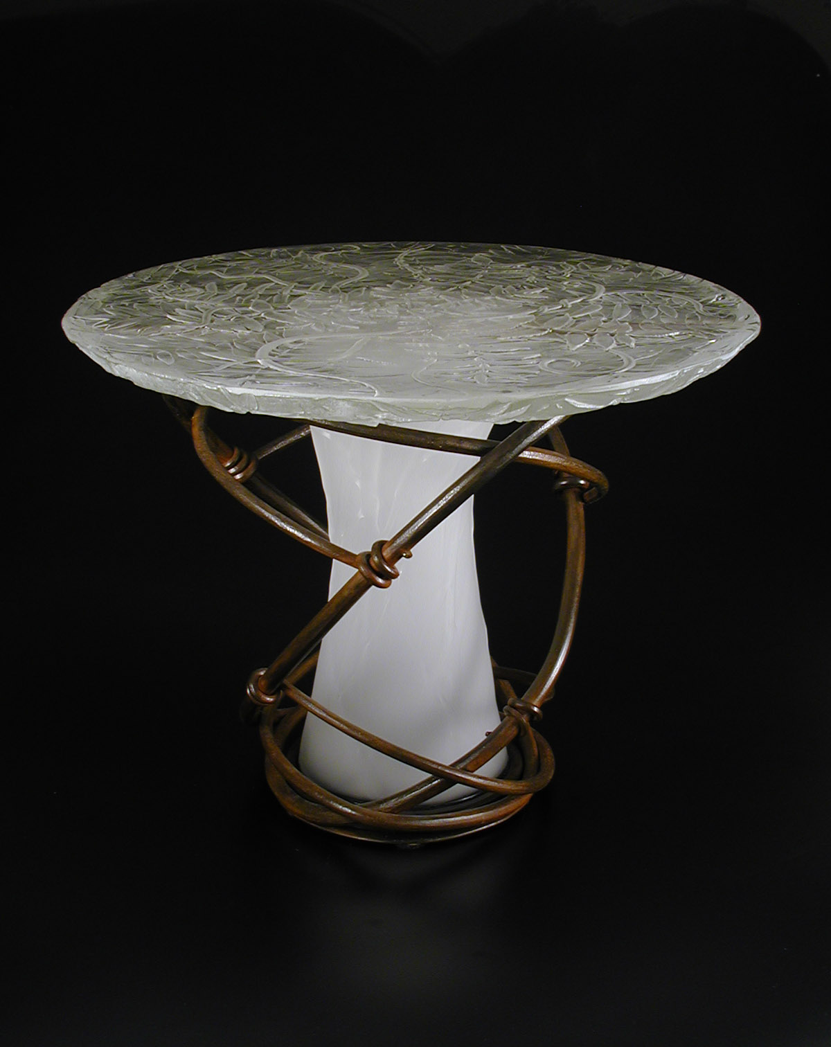Table with cast glass top containing sumac pattern, base of forged iron twined vines around blown glass center.