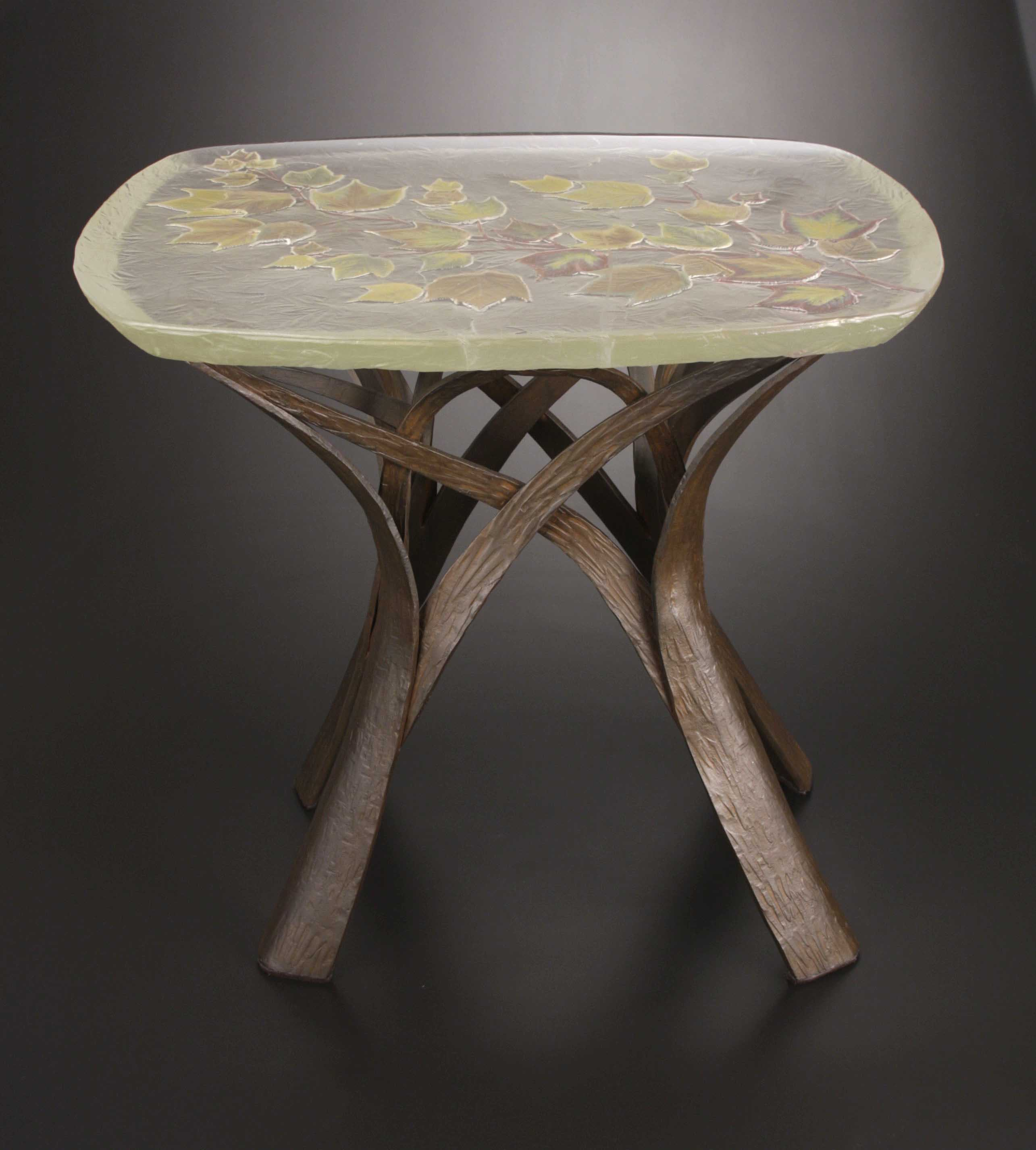 Table with glass top with lustered maple leaves, base of forged steel.