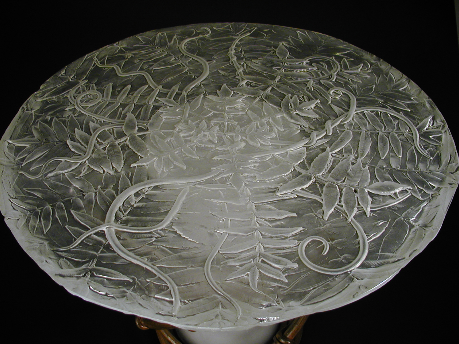 Top view of table with cast glass top containing sumac pattern, base of forged iron twined vines around blown glass center.