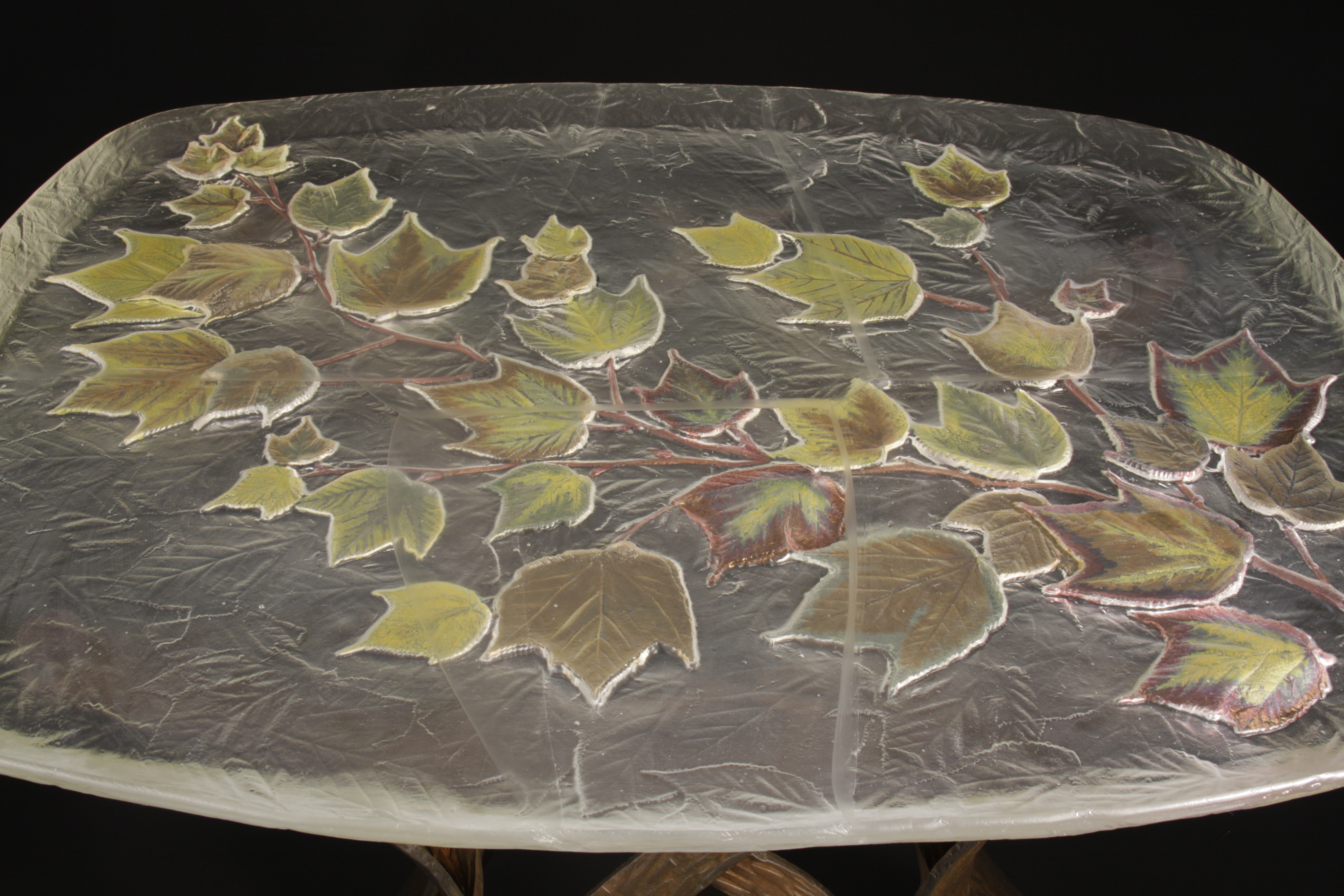 Top view of table with glass top with lustered maple leaves, base of forged steel.