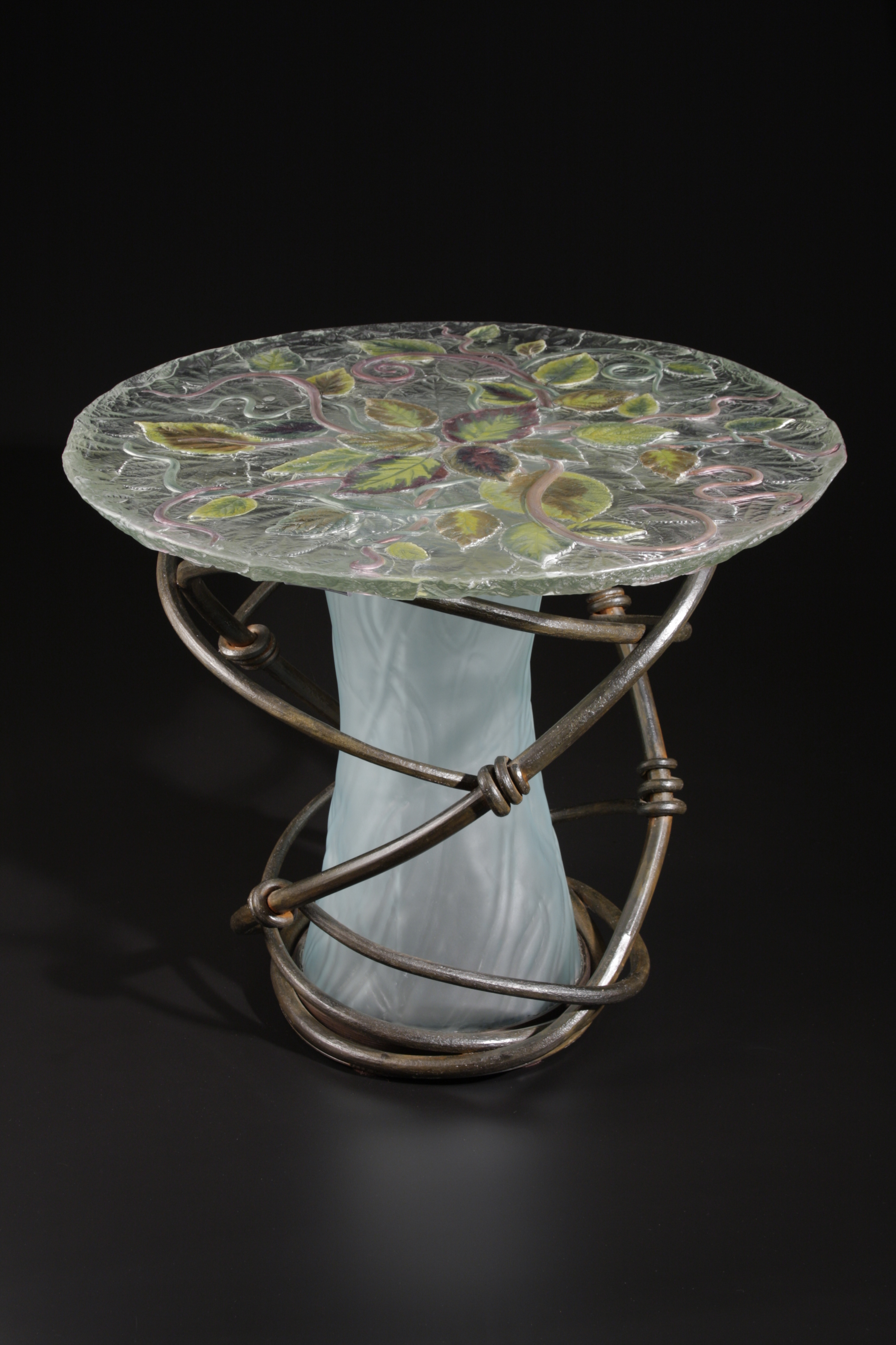 Table with cast glass top with lustered leaves. Glass center surrounded by forged steel vines.