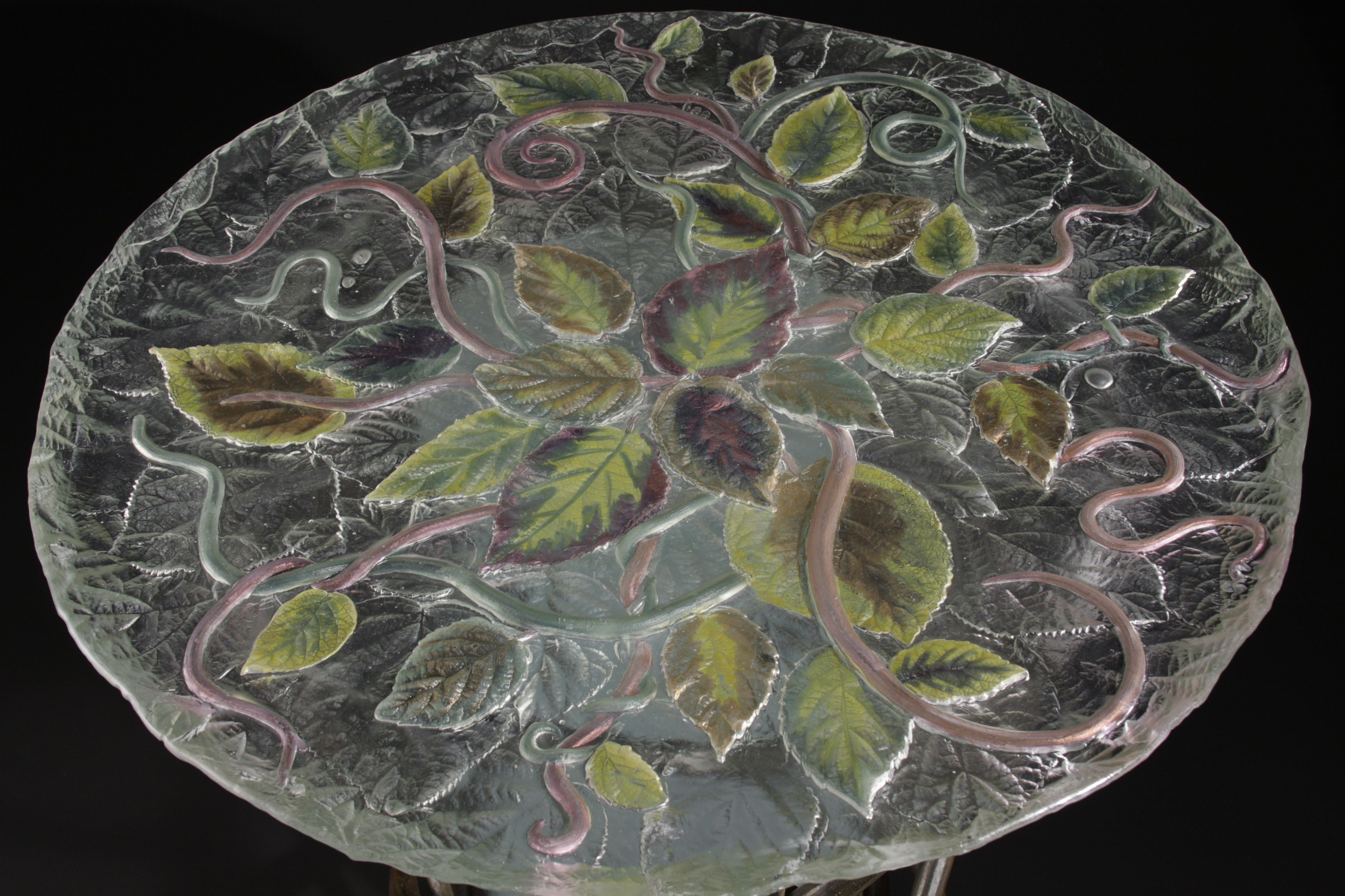 Top view of table with cast glass top with lustered leaves. Glass center surrounded by forged steel vines.