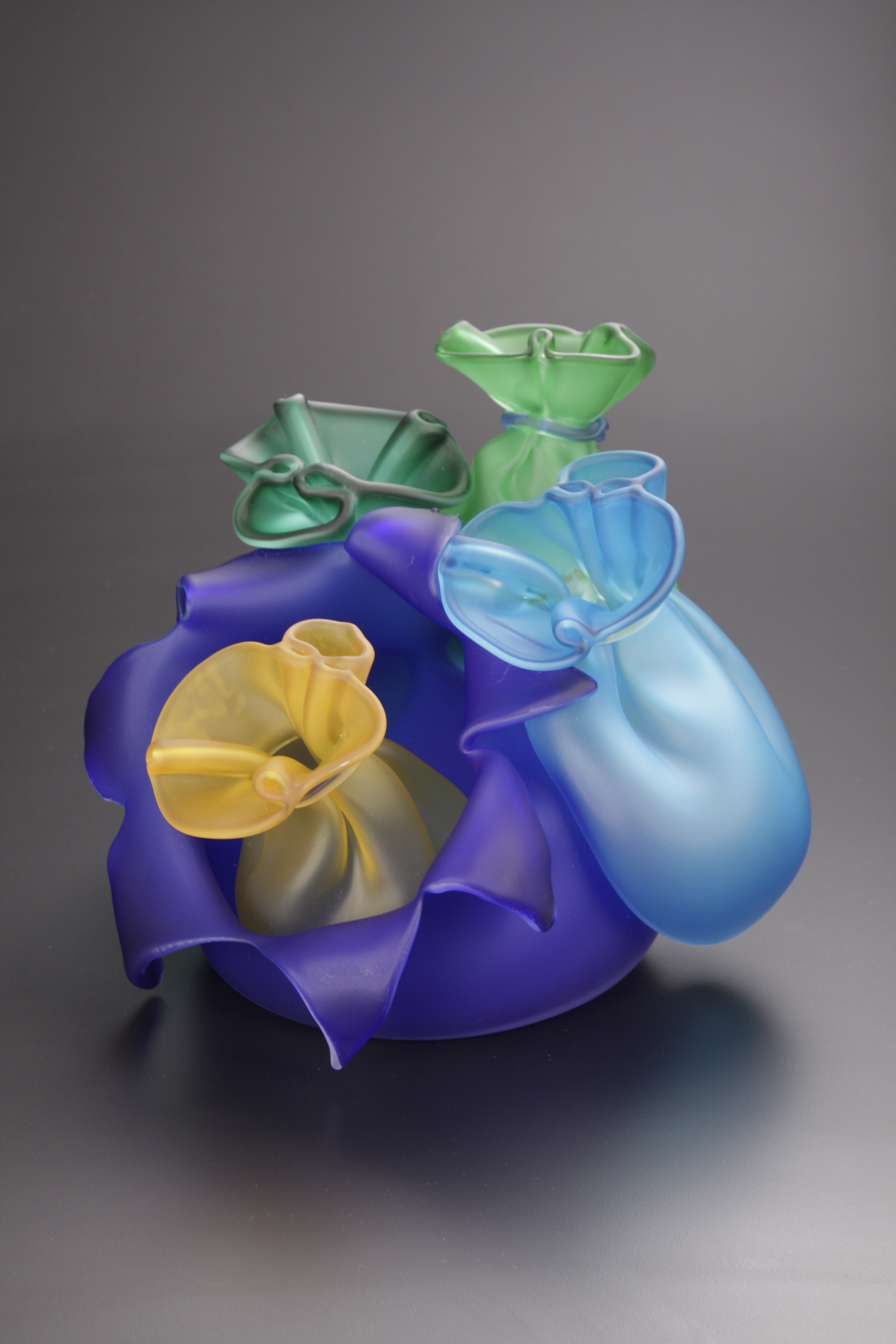Glass sack with glass bags around it in blue, green, and amber.