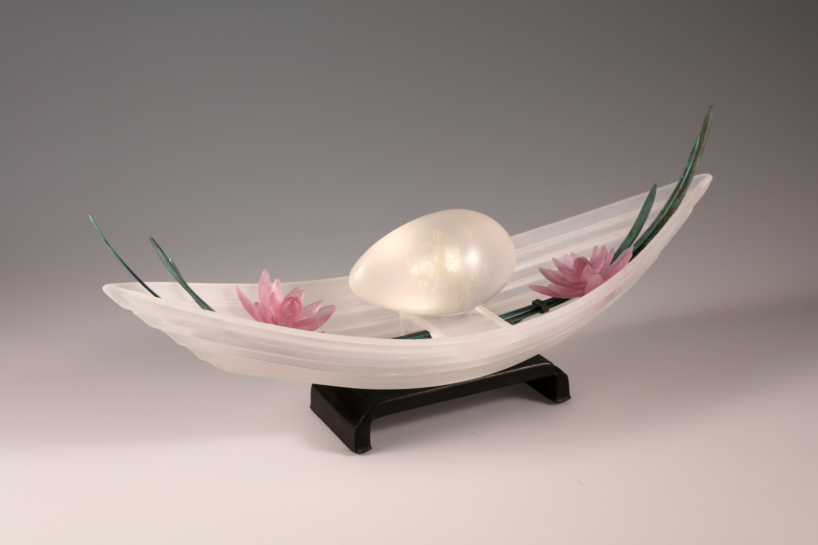 Sculpture of cast glass boat and lavender flowers with bronze leaves on steel base.
