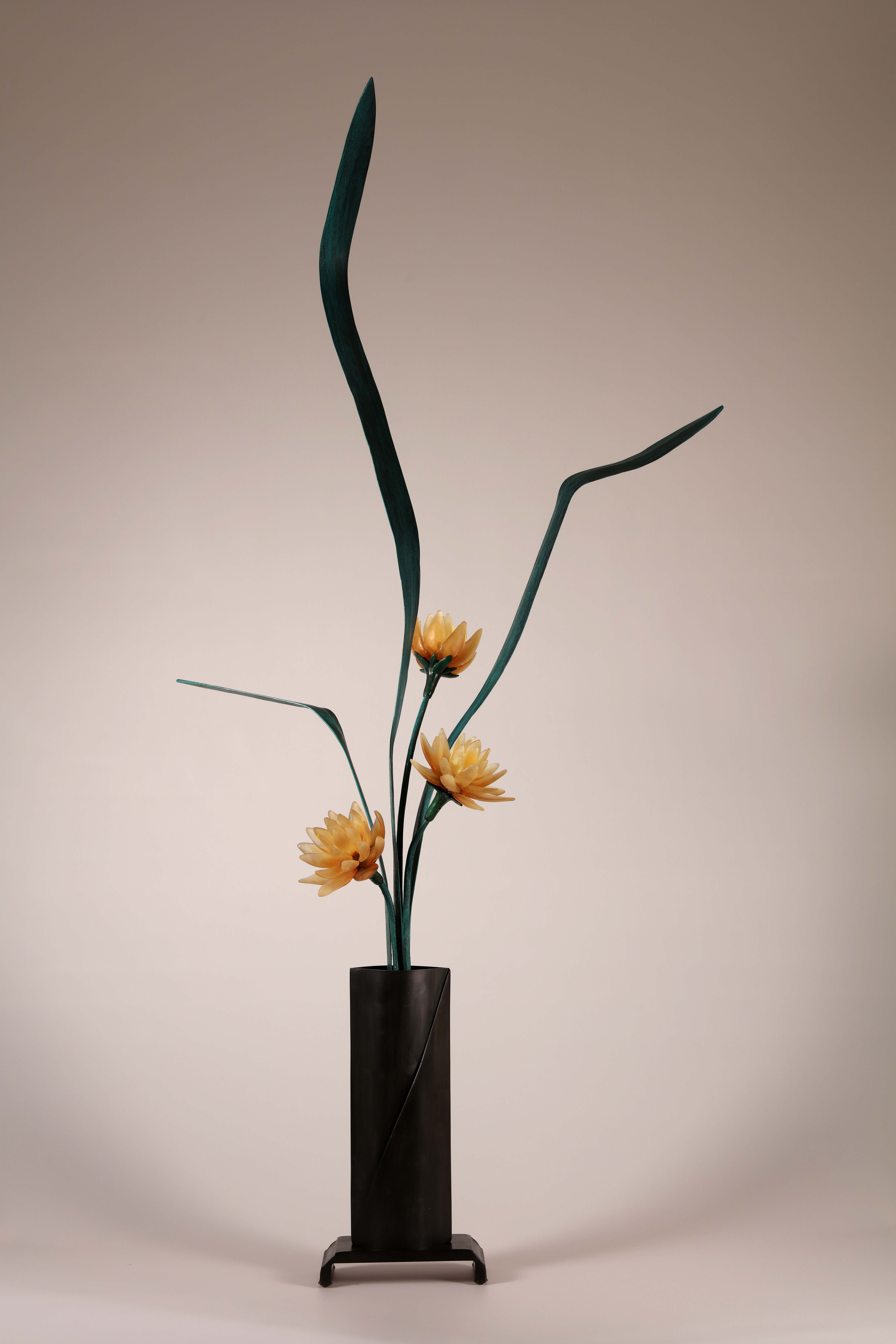 Right side of sculptural flower arrangement in cast glass with amber flowers, green steel leaves, tall vase in deep brown.