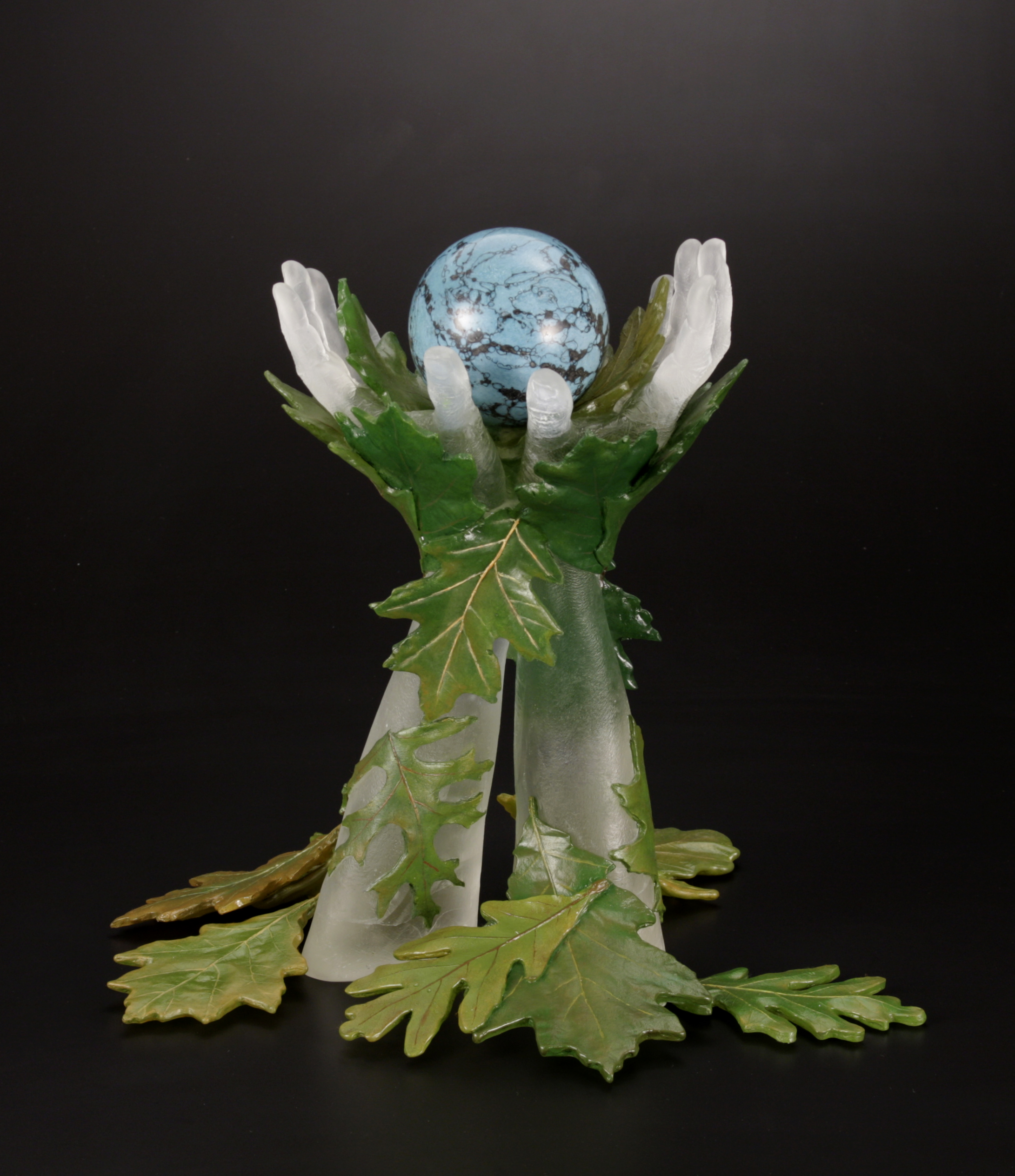 Sculpture of hands cast in clear glass surrounded by oak leaves painted with oil paint holding turquoise sphere.